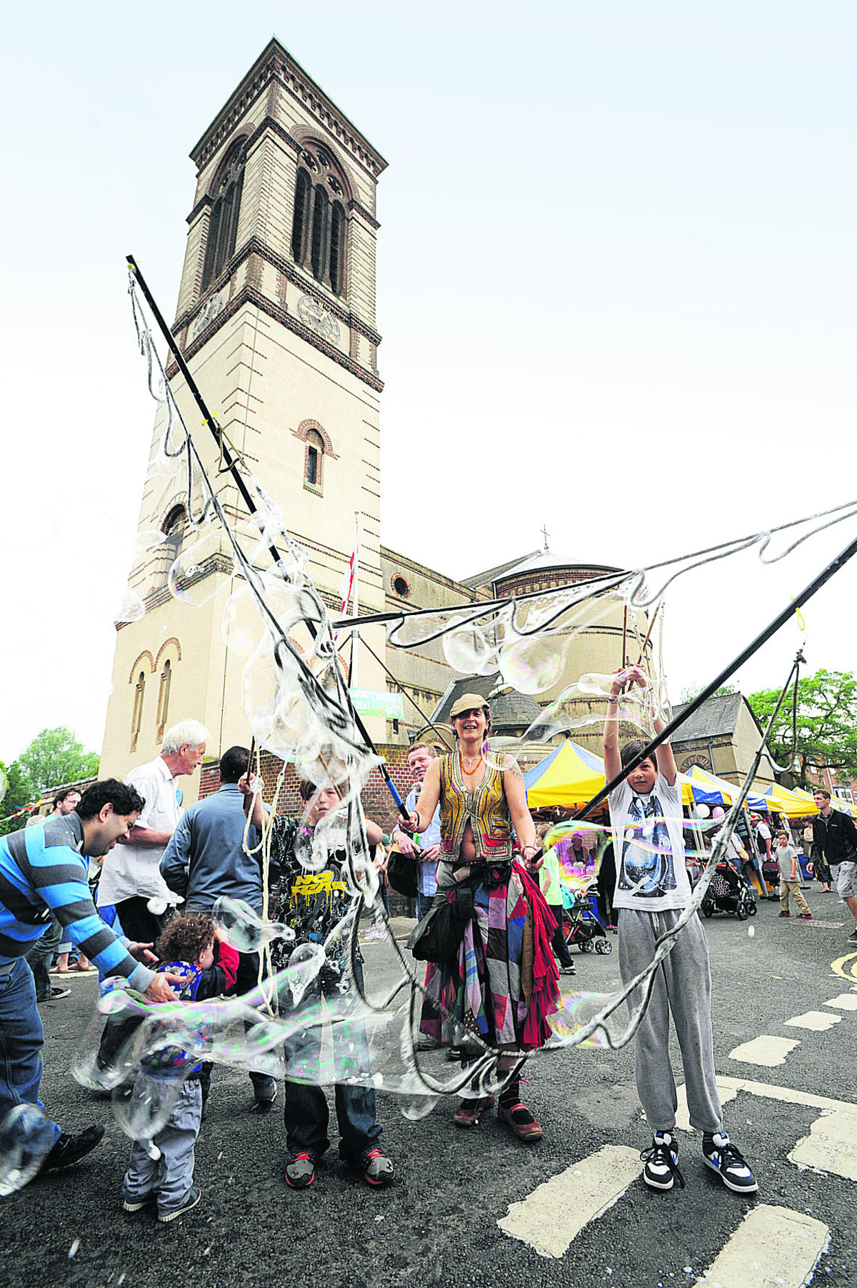 Lara Love creates some giant bubbles in front of St Barnabas Church during Jericho Street Fair