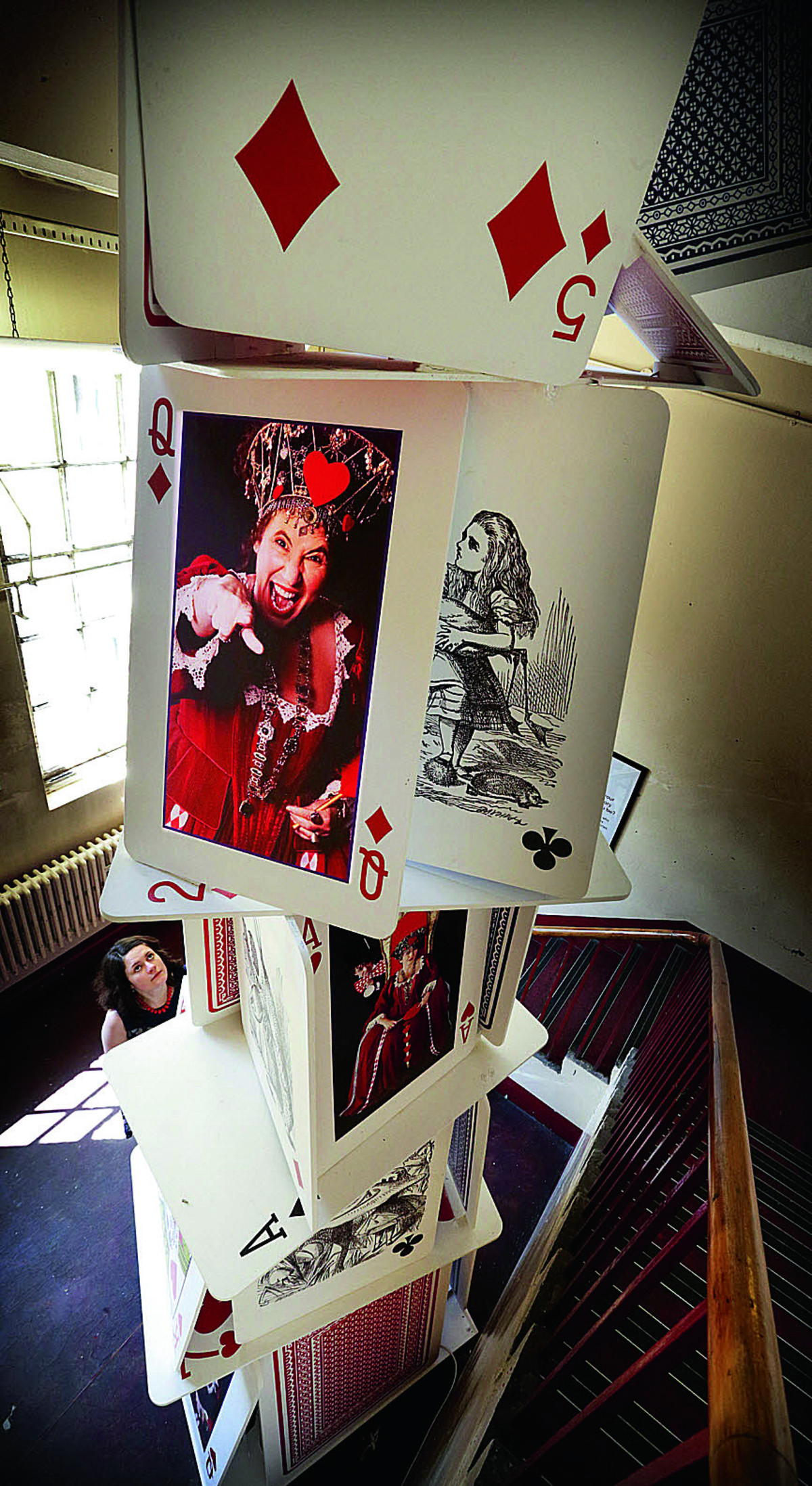Alex Coke, of the Story Museum, looks up at a tower of cards depicting Horrid Henry author Francesca Simon playing the Queen of Hearts             Picture: OX67904 Damian Halliwell