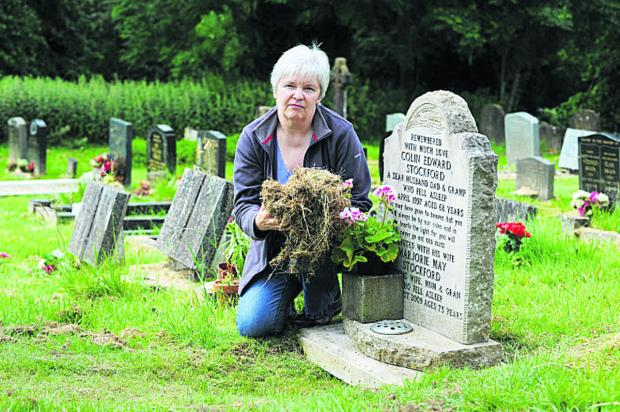 Oxford Mail: Colleen Green with the grass cuttings beside her parents' grave