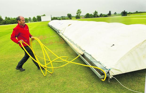 Banbury groundsman Sean Cranley makes sure the wicket is covered before the start of their delayed Division 1 match against Oxford on Saturday