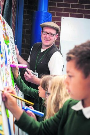 Artist Neill Cameron guides Church Cowley St James pupils including Dionatae Ellis, 8, in their artistic talents