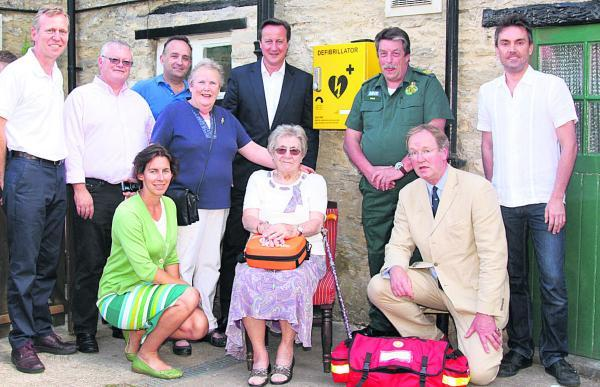 Prime Minister David Cameron and Dick Tracey, next to the defibillator box, with Hailer residents and GP Dr Robin Carr, front, right
