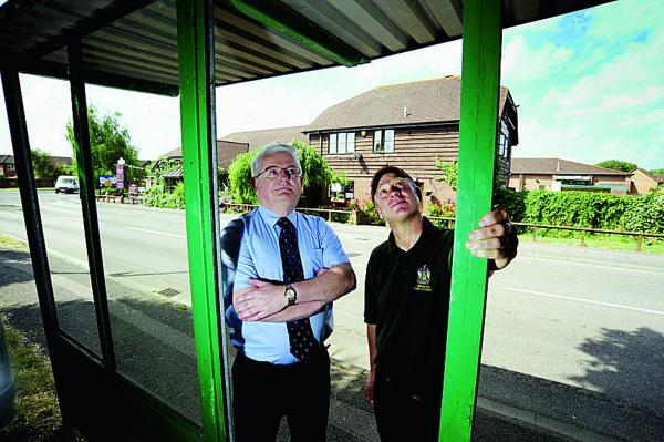 Oxford Mail: From left, Steve Rich, Head of Services and John Morris, from the Abingdon Town Council Works Team, inspects a bus shelter in Peachcroft Road that has had three of its windows smashed by vandals