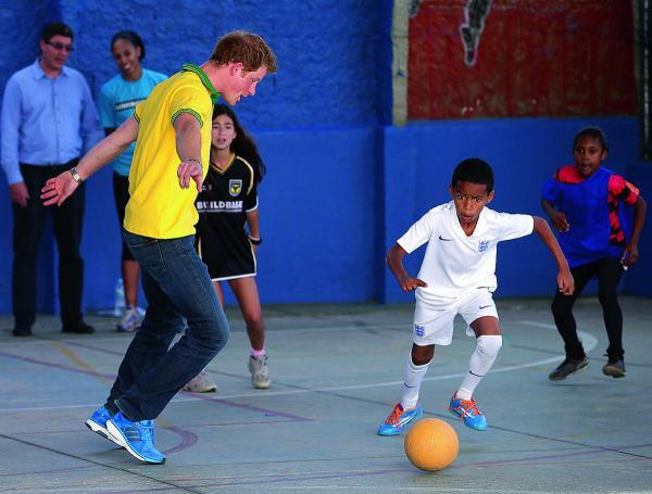 Oxford Mail: Prince Harry plays football at the ACER Charity for disadvantaged children in Sao Paulo, Brazil. He is watched by a fellow player wearing an old-style Oxford United shirt.             Picture: Chris Jackson/ Getty Images