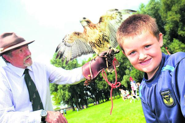 Oxford Mail: Charlie Mayhew, six, and Terry Large from Falconry Displays with a North American Redtail