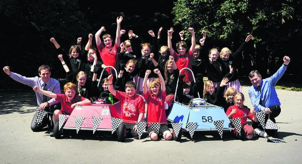 Oxford Mail: A team of children from The Hendreds Primary School took on more than 70 teams from around the country racing their electric cars at Goodwood. The group are pictured with teachers Jamie Veness, left, and Chris Savage