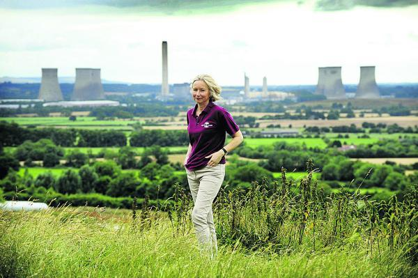Jayne Manley from the Earth Trust on top of Wittenham Clumps with Didcot Power Station behind.  Picture: OX68683 David Fleming