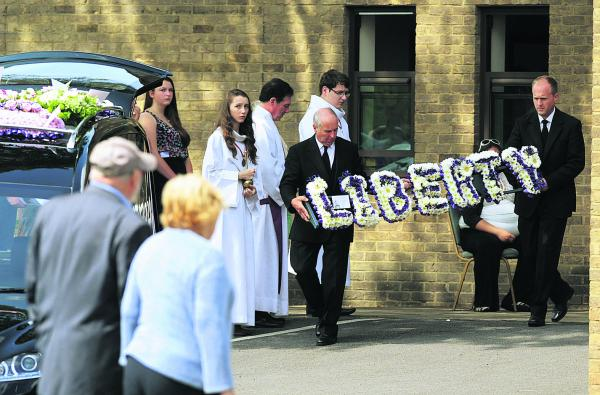 A floral tribute is carried from the church  following Liberty Baker's funeral yesterday