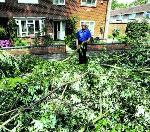 Abraham Clarke, 85, of Ladenham Road, stands amongst branches, which broke away from a tree next to his home during the storm and landed in his front garden