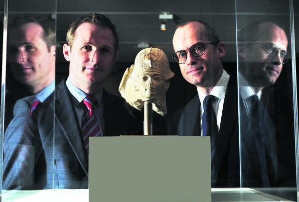 Co-curators Liam McNamara, left, and Dr Paul Collins with a statue of the head of Tutankhamun made out of limestone during his reign between 1332 and 1322BC