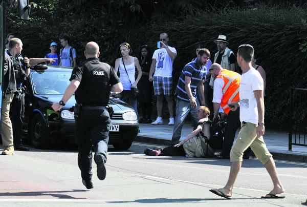 A man sits in the road, top, after being struck by a VW Golf as he crossed the road at Folly Bridge, Oxford, yesterday