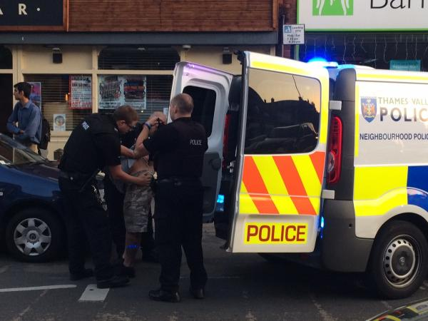 A man is put into the back of a police van on Cowley Road