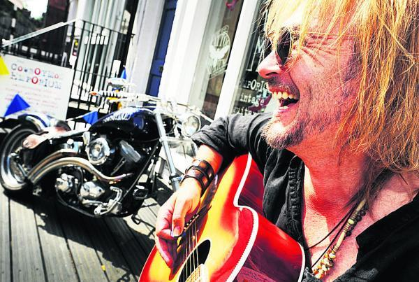 ames Salter enjoying the sun playing guitar and singing to passers-by outside his Walton Street shop Cowboymod