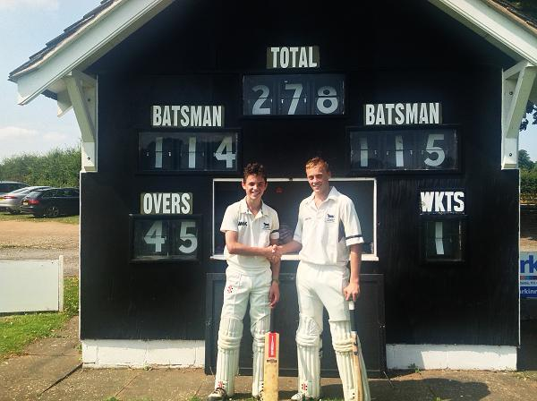 Tom Price (left) and Harrison Ward celebrate their centuries for Oxfordshire Under 14s in front of the scoreboard at Shifnall CC