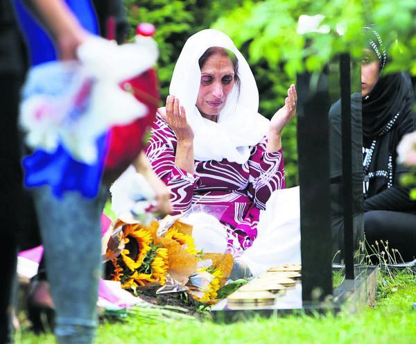 Mehfooz Akhtar at the graves of her children Anum and Majid at Botley Cemetery yesterday       Picture: Damian Halliwell