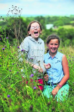 Niamh Gara, left, and Alice Steuart-Feilding, both 11, enjoy wild flowers in the meadow