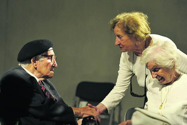 Gilbert King shakes hands with Holocaust survivor Susan Pollack, while fellow survivor Renee Salt