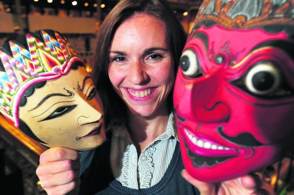 Helen Adams holds up two Indonesian masks for use in the Pitt Rivers pop-up museum