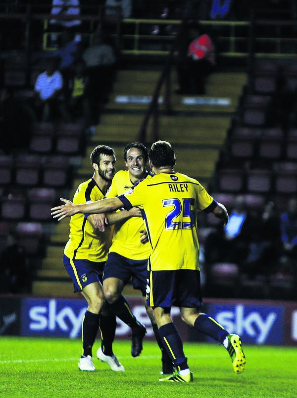 Danny Hylton celebrates his dramatic late winner with Joe Riley and Jon Meades as Oxford United stunned Bristol City in the Capital One Cup last night