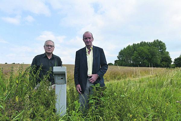 Stuart Harrison, chairman of the North Witney Action Group, left, with Graham Knaggs, chairman of Hailey Parish Council, by a camera which is used to monitor water levels in a field off Eastfield Road, Witney