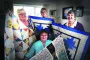 Mary Simmonds, front, with, from left, Cynthia Peddy, Carole Pack and Ruth Jones and their quilts
