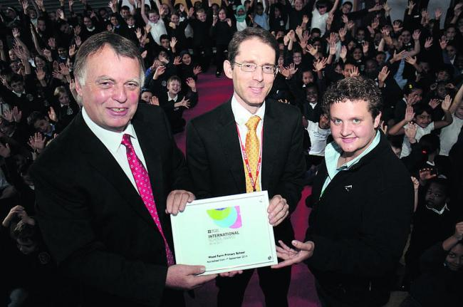 Andrew Smith MP, left, presents the award to Wood Farm headteacher David Lewin, centre, and South African visitor Ilze Van de Vyver