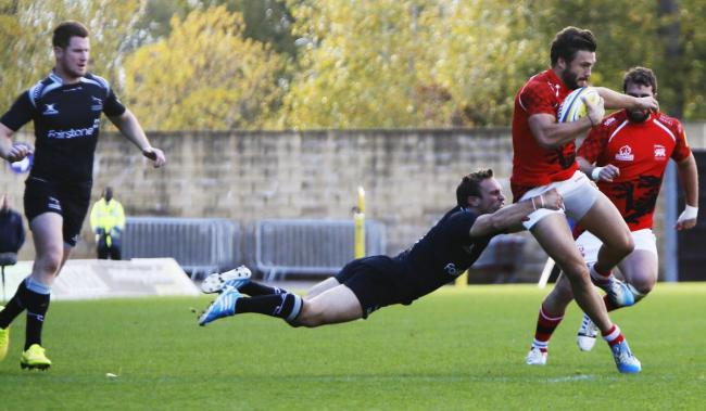 London Welsh's Seb Stegmann is held up by this full-stretch tackle from Mike Blair