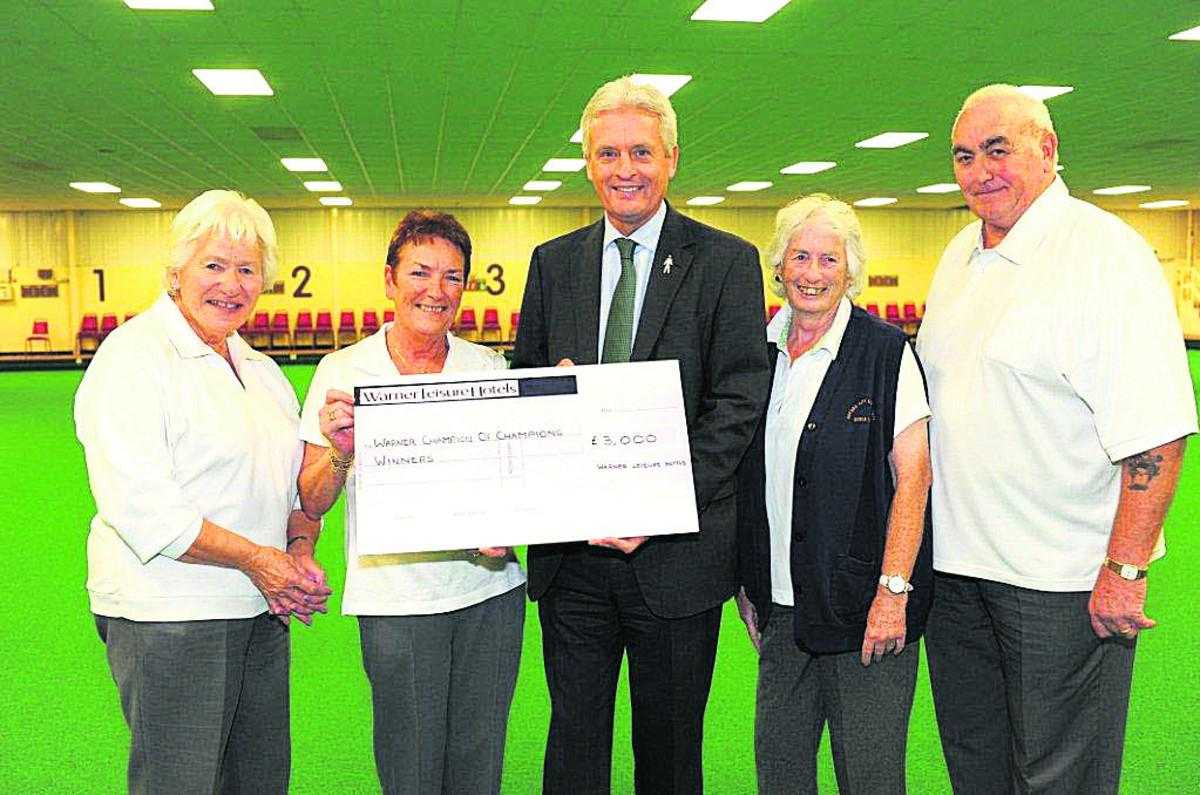 England indoor bowls captain Andy Thomson presents the winner's cheque to, from left: Vicky Harrison, Pat Bourne, Patricia Strange and Tony Bourne