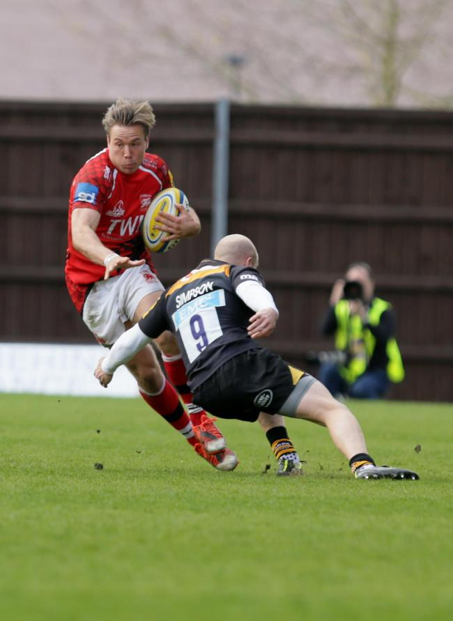 London Welsh's Will Robinson is tackled by Wasps' Joe Simpson