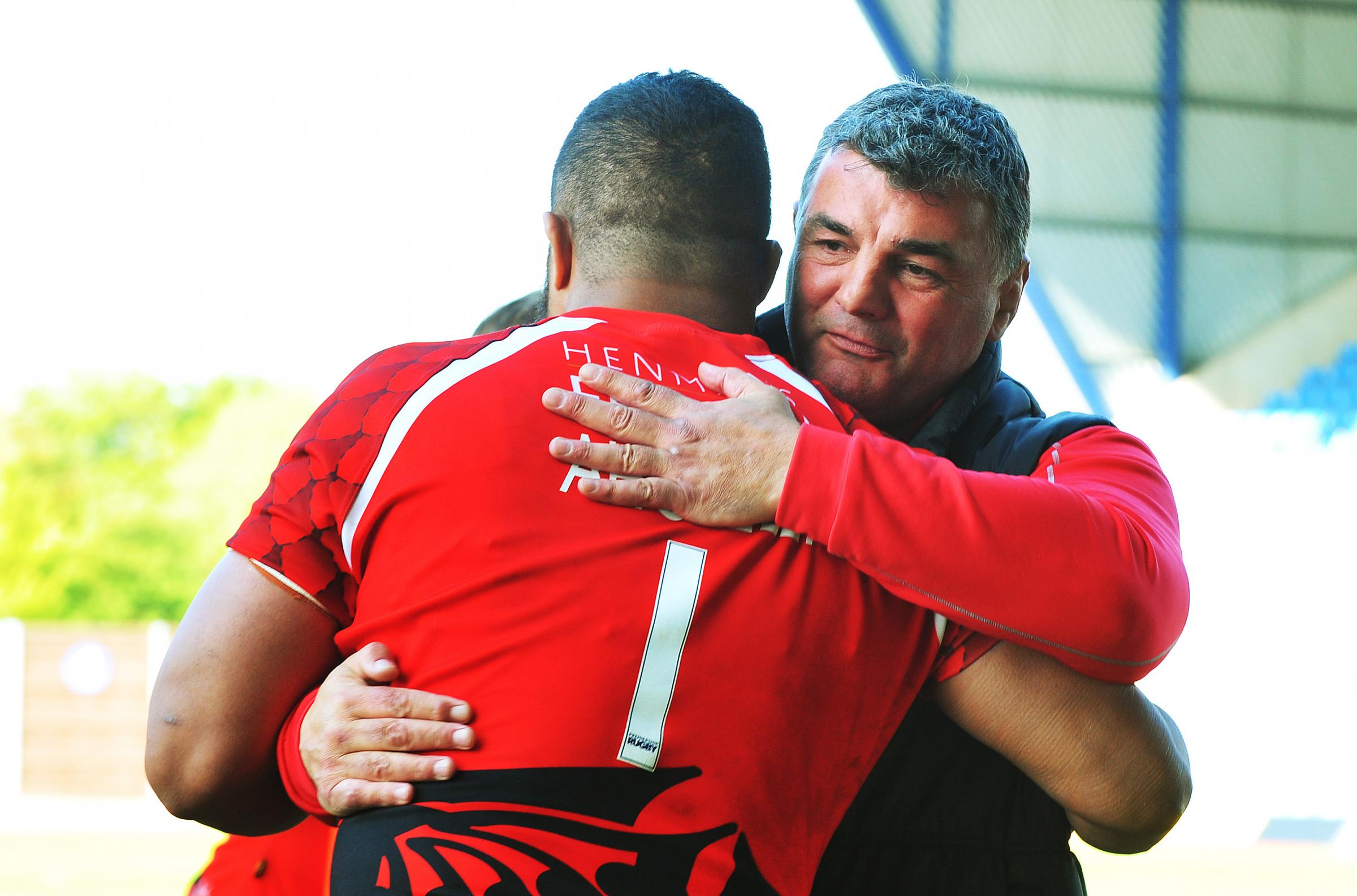 London Welsh head coach Rowland Phillips gives Eddie Aholelei a consoling hug after Saturday's defeat