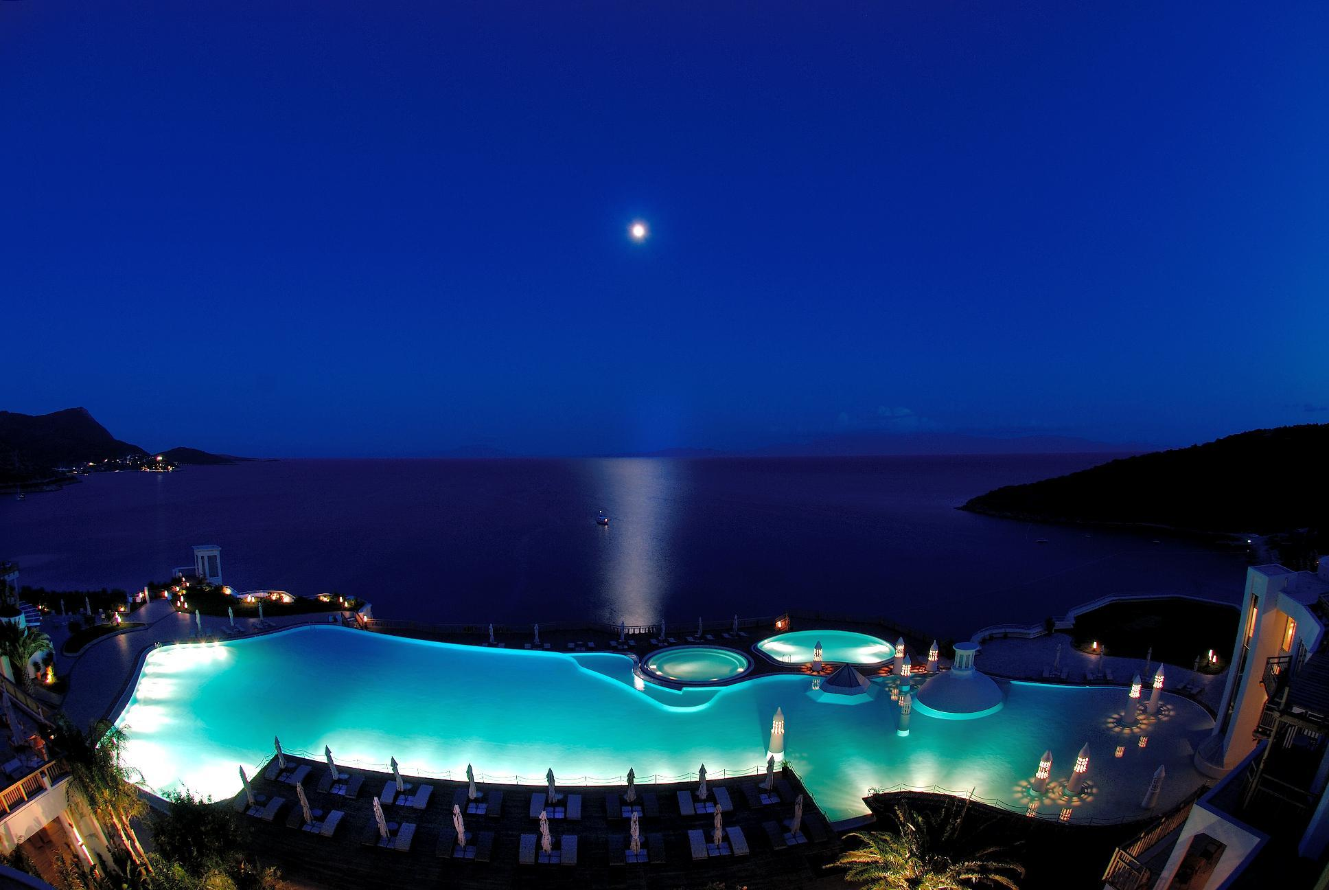 The view over the pool and to the sea beyond at night