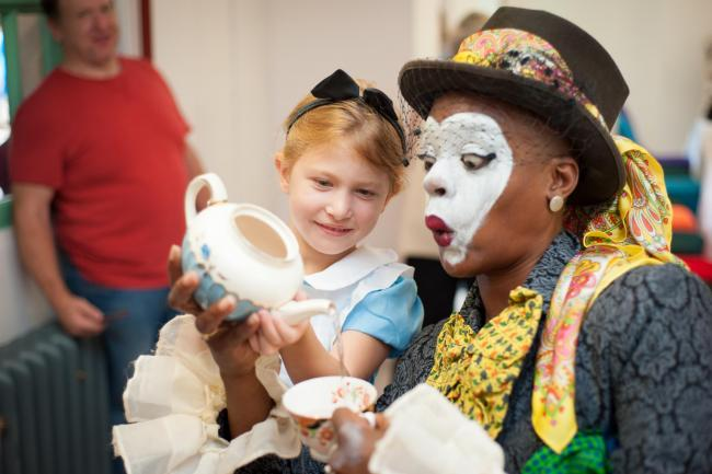 Lila Cherny pours tea for T'nia Miller, of Teatro Vivo, playing the Mad Hatter in a recreation of the Tea Party