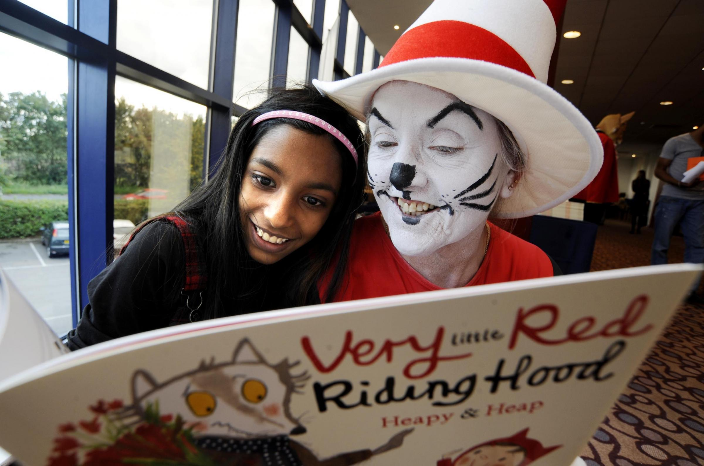 Joy of books: Karen Fernandes-Pauscar, 10, reads with Anne Walton, dressed as The Cat in the Hat, at yesterday's event