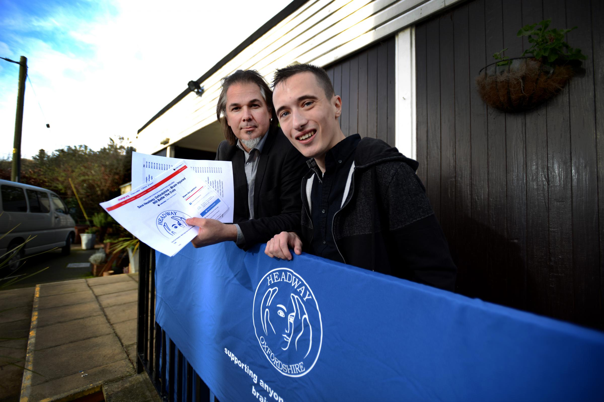 Headway chief executive Jamie Miller, left, with Andrew Baker and his petition
