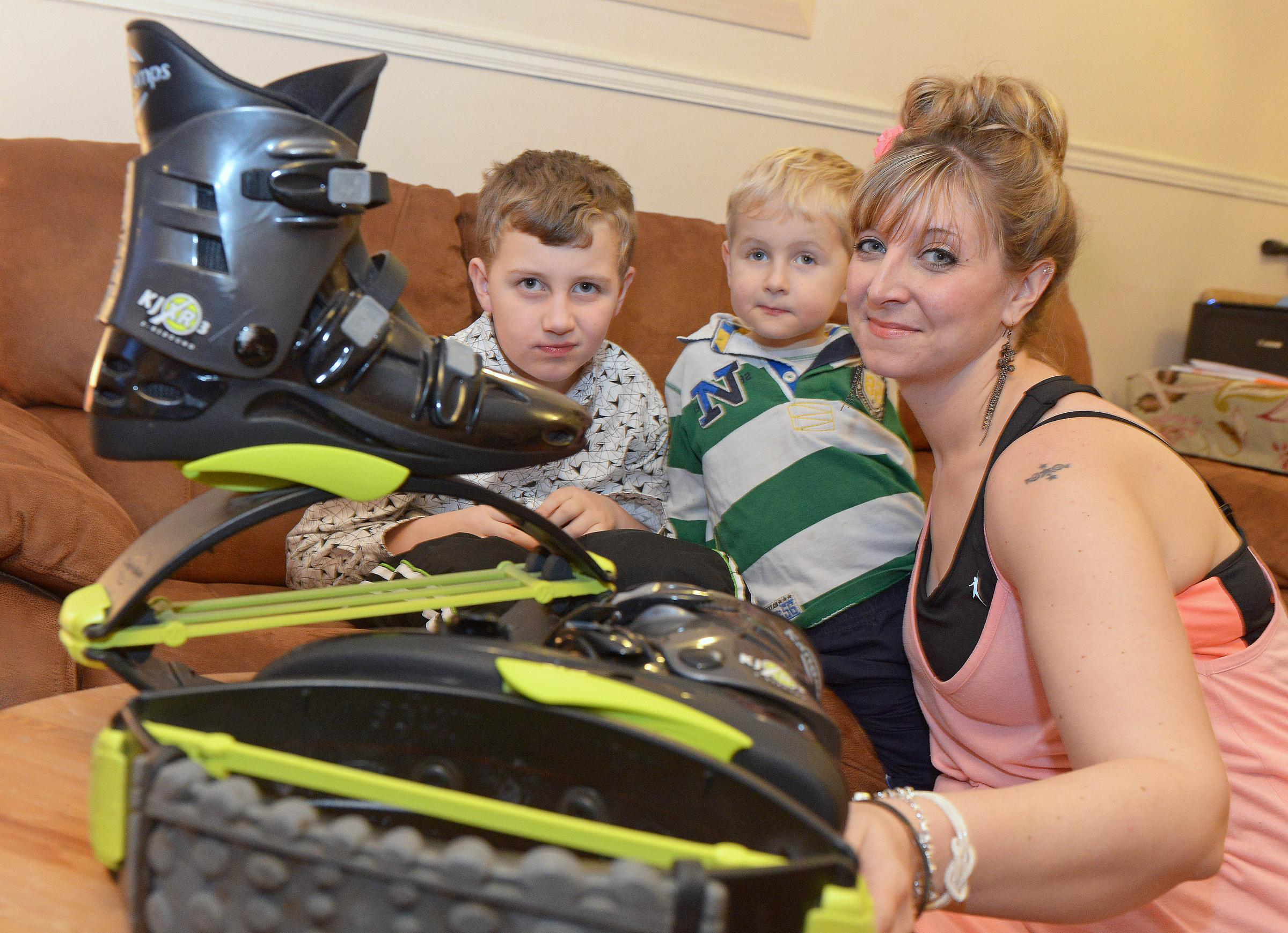 Lisa Stride-Purves with sons Ethan, left, and Isaac and the special 'jump' boots she wears to train for the run