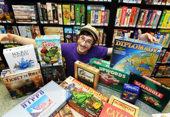 Manager Simon Read with retro and new board games at Thirsty Meeples