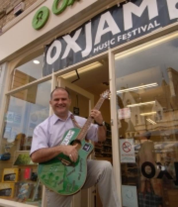 Dave de Paeztron at the Oxfam shop in Broad Street, with the travelling green guitar