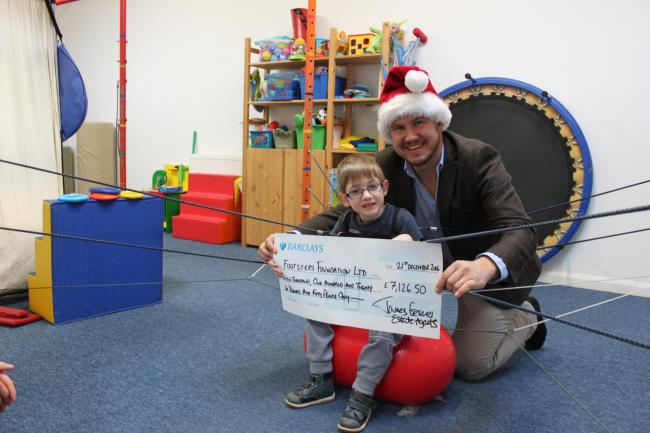 Estate agent James Gesner pictured with young Lewis at the Footsteps centre in Dorchester on Thames