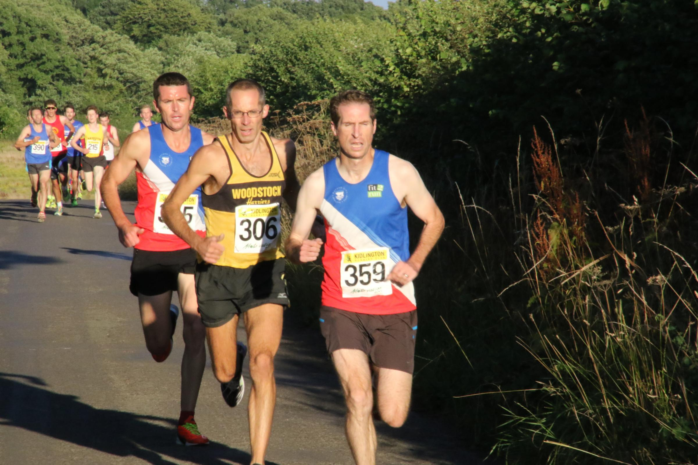 Woodstock Harriers's James Bolton (middle) battles it out with Les Newell (front) and Tegs Jones at Combe Picture: Barry Cornelius