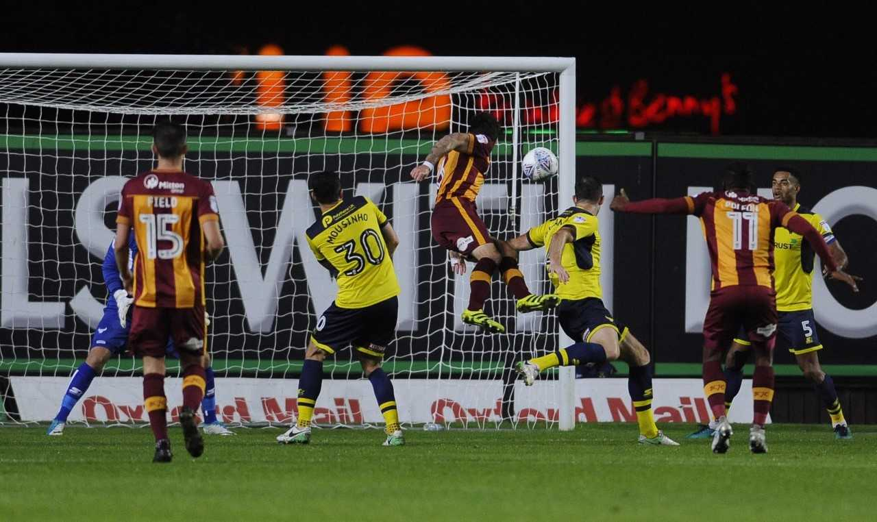 Romain Vincelot (centre) heads in Bradford's stoppage-time equaliser Picture: David Fleming