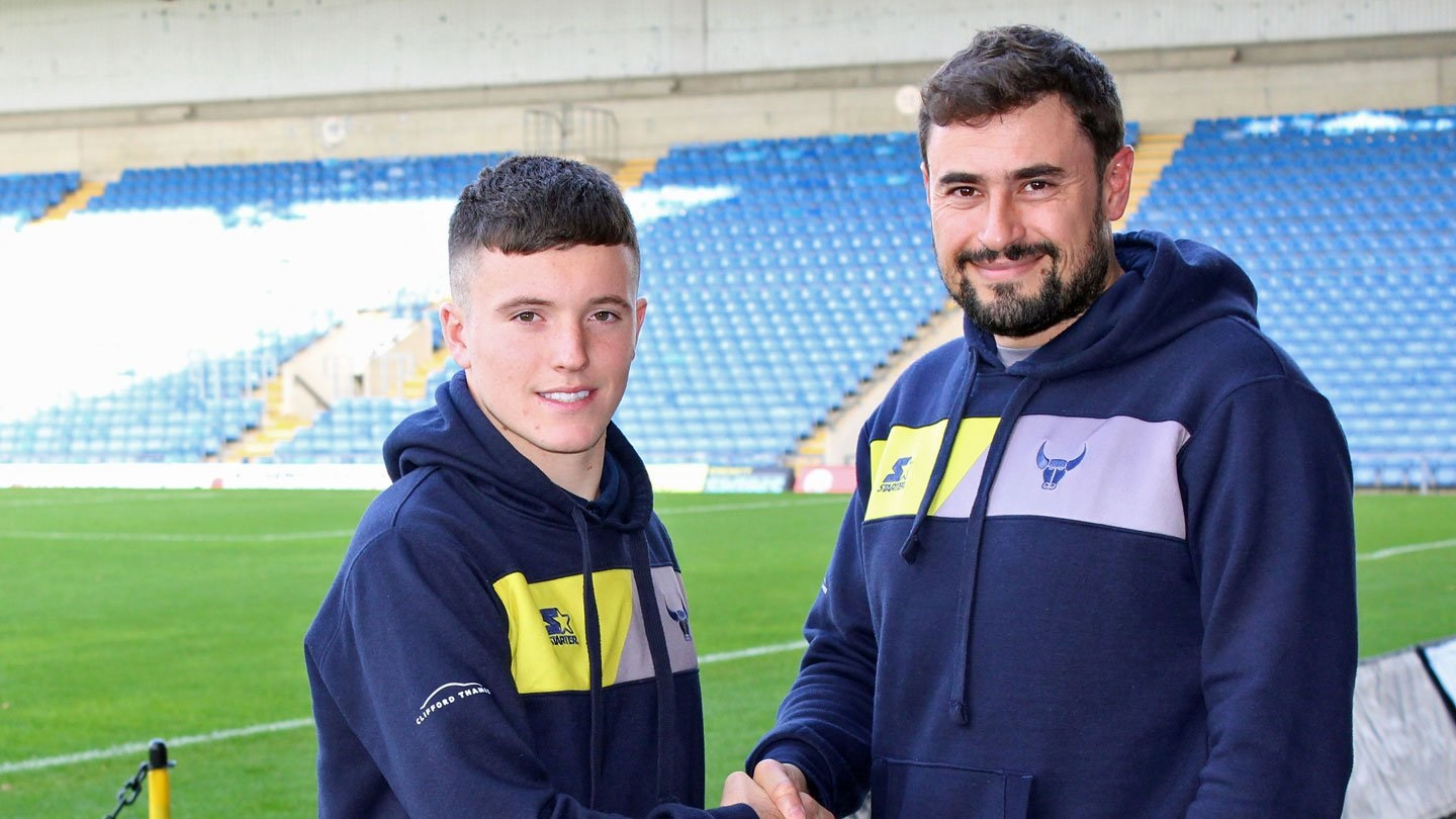 Owen James shakes hands with Oxford United manager Pep Clotet after signing his professional contract