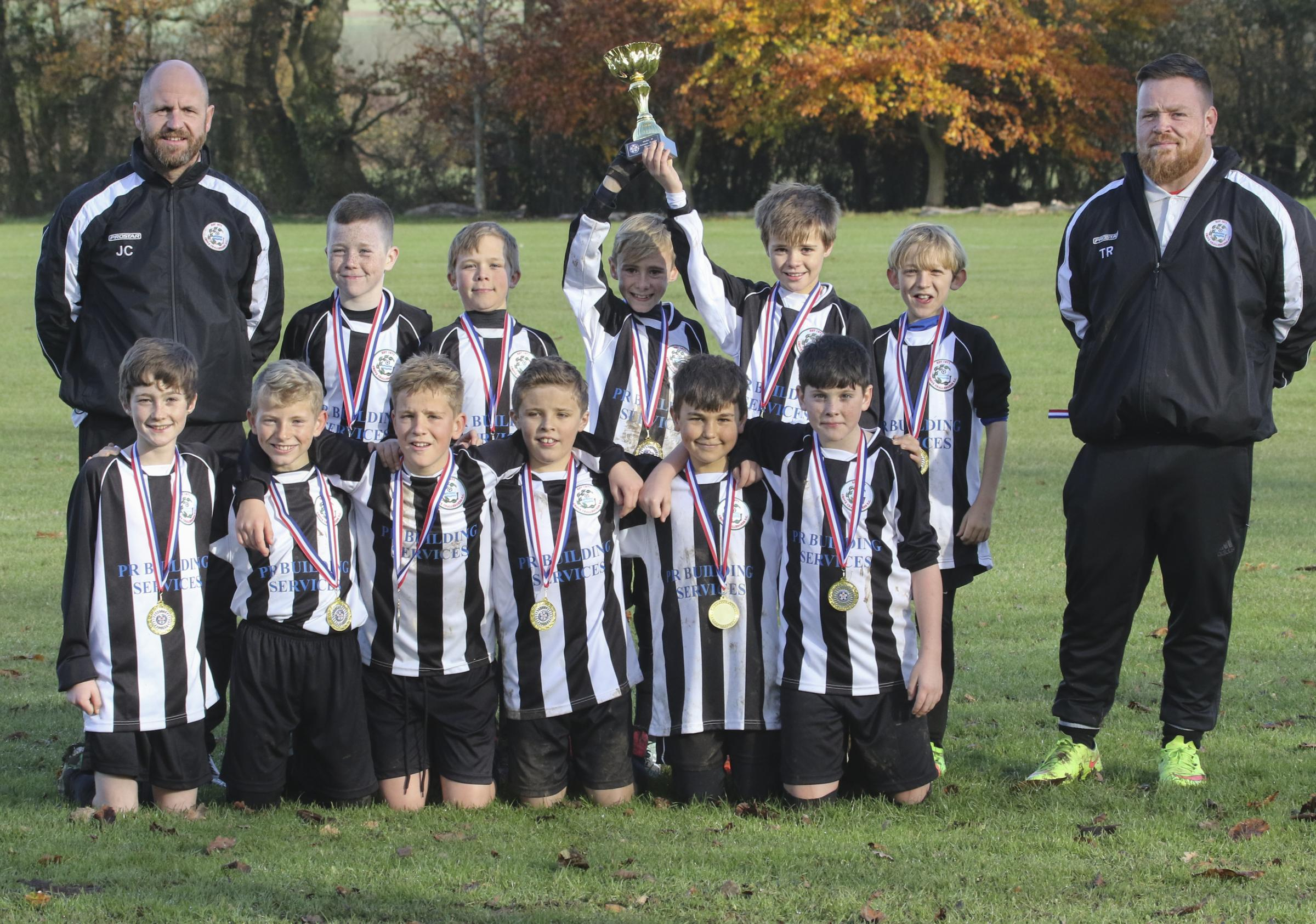 SILVERWARE: Grove Challengers White celebrate after winning the Oxford Mail Youth League Under 11 Supplementary Cup. The team who are sponsored by PR Building Services, beat Headington 6-2 in the final. The team, pictured with coaches Tony Reed and Jason