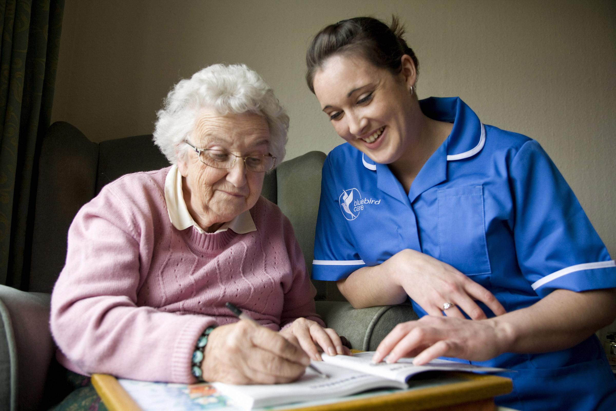 A Bluebird Care worker with a pensioner. Picture Bluebird Care