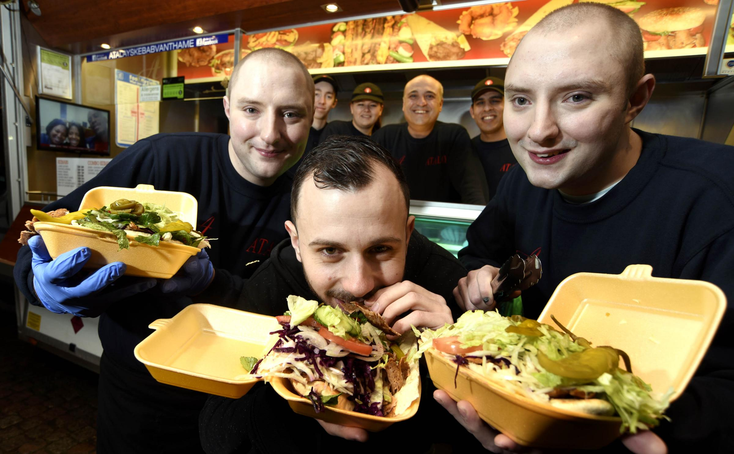 Kebab lover Dom Stanway-Williams, tucks into a kebab from Atalay Kebab van. L-R, Jason Atalay, Dom Stanway-Williams and Joshua Atalay.