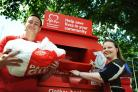 City councillor Tom Hayes and Oxford professor Jemma Hopewell at the BHF big red bin in Morrell Avenue. Picture: Jon Lewis.