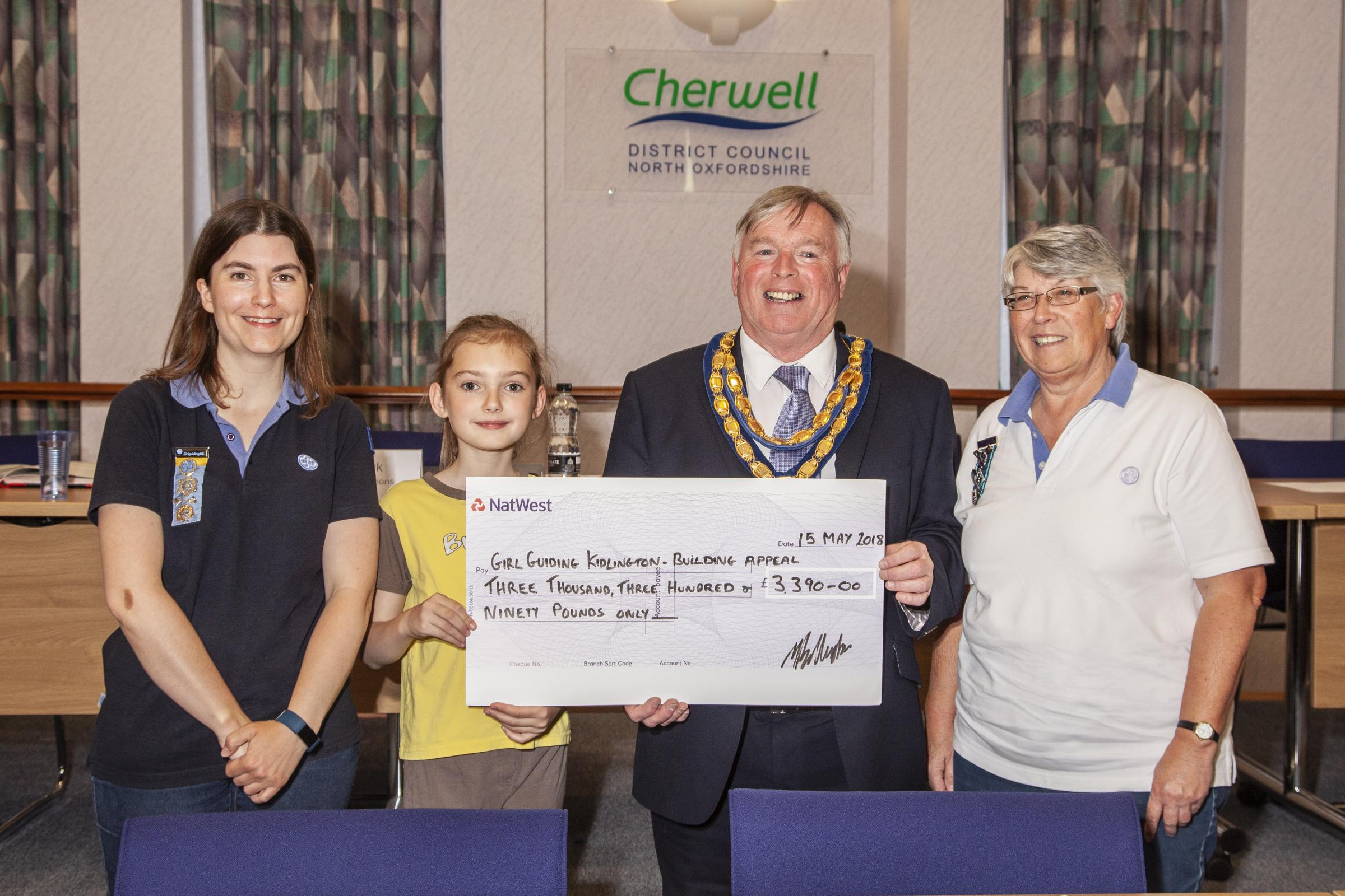 Cherwell District Council chairman handing over the share of £19,000 to Kidlington Girl Guides after raising a record-brekaing amount for charity