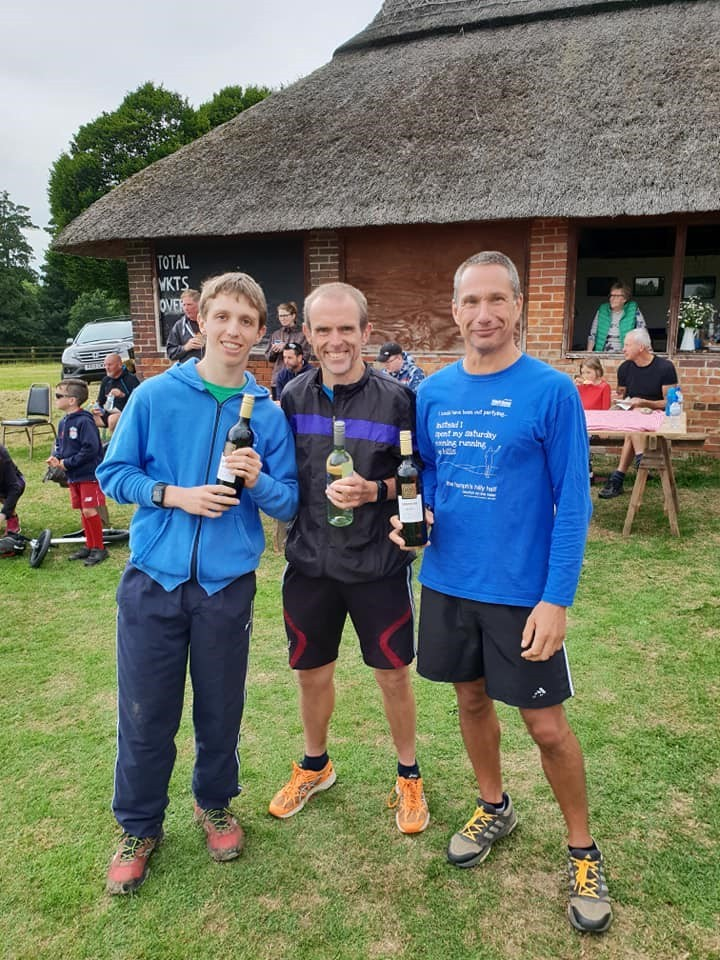 IN THE BLOOD: Witney's Tony Lock (centre) is delighted at winning the Steeple Barton 5km ahead of his son Matt (left), while Graham Ferris (right) shows off his bottle of wine for finishing as the first vet 50 in the 10km event