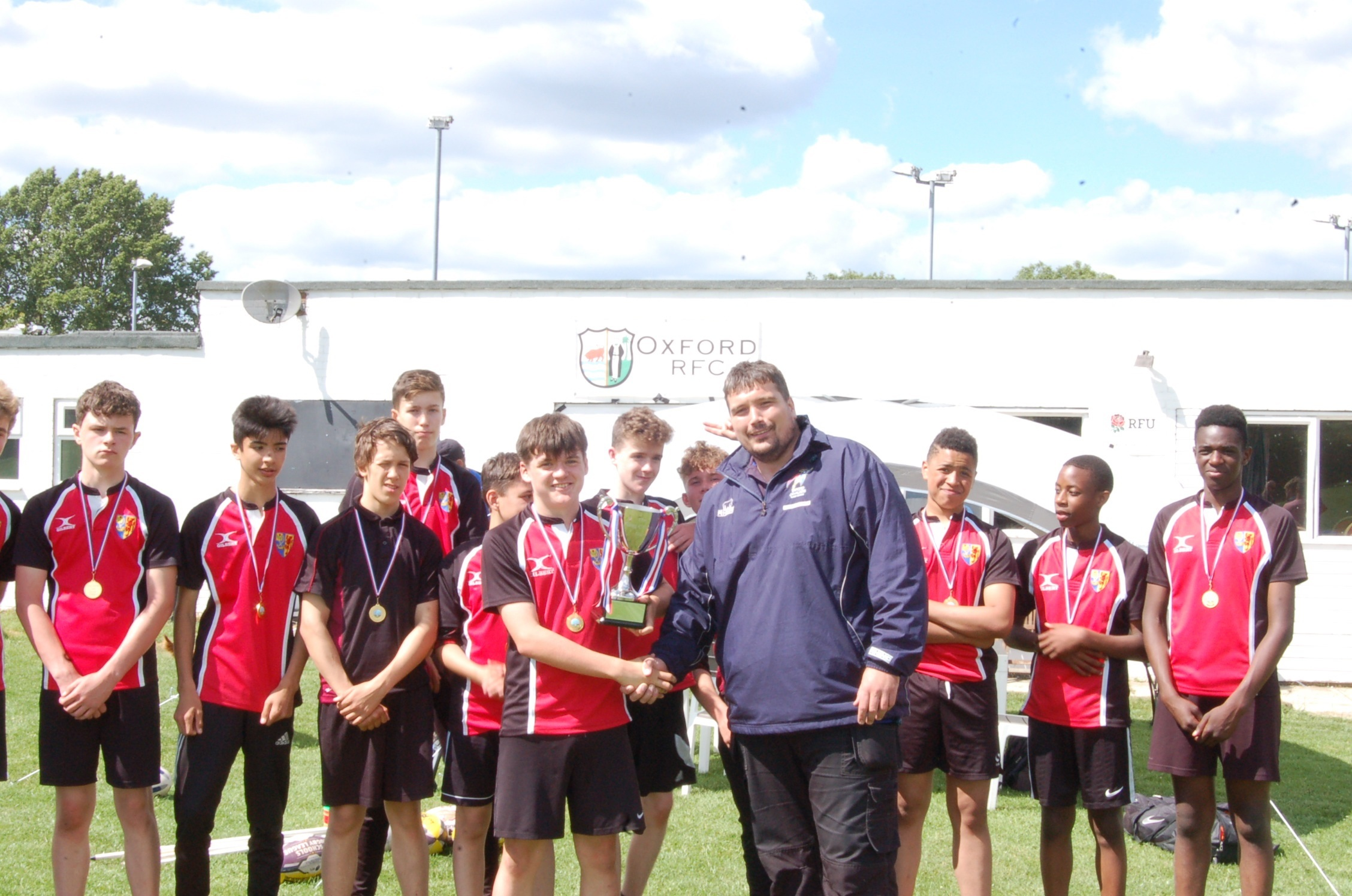 CHAMPIONS: Bartholomew School captain Jacob Moir is presented with the King Charles Cup by Oxford Cavaliers' head of youth development Jamie Jones