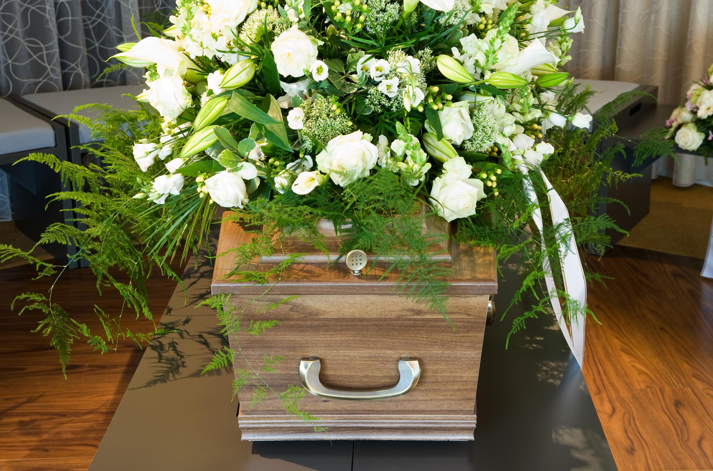 A coffin in a morgue with a flower arrangement.