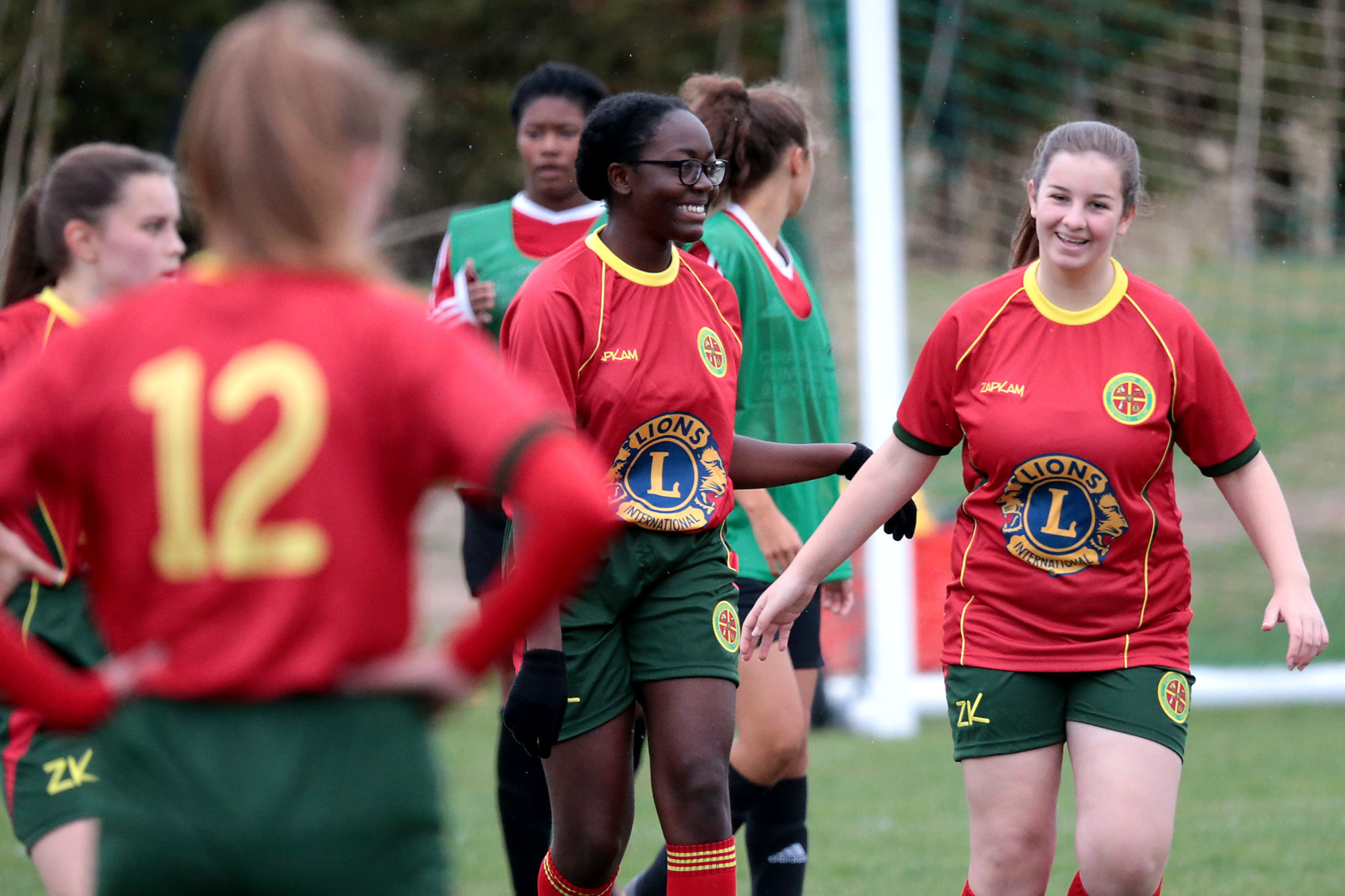 DELIGHT: Elizabeth Mate (centre) celebrates opening the scoring for Carterton Under 16s during their win over Barton United Picture: Ric Mellis
